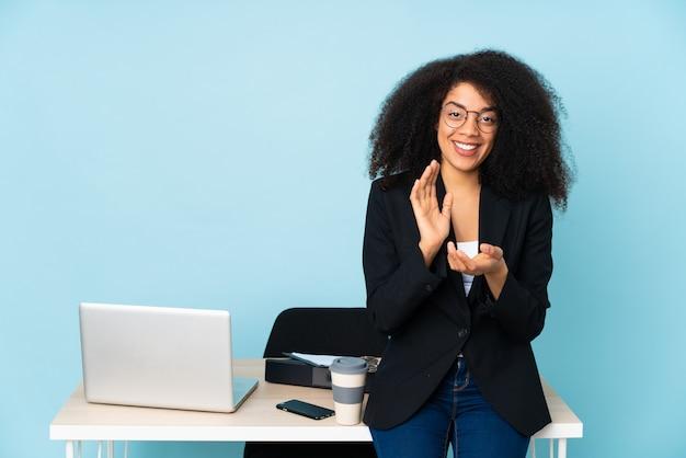 Mujer de negocios trabajando en su lugar de trabajo aplaudiendo después de la presentación en una conferencia