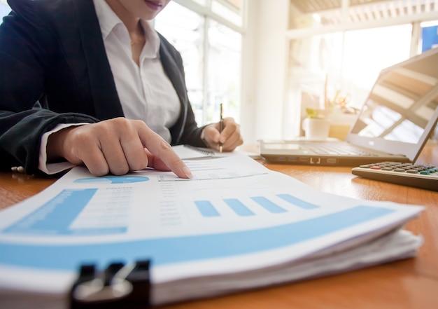 Mujer de negocios en trabajar con informes financieros y computadora portátil en la oficina.