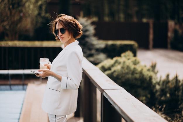 Mujer de negocios en traje blanco al aire libre