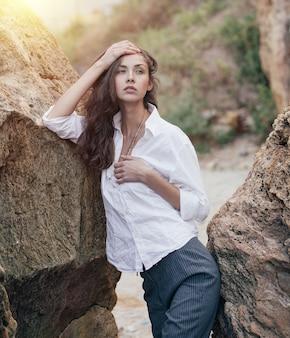 La mujer de negocios en el traje y la camisa blanca que se colocan cerca de piedra grande en el mar costaron