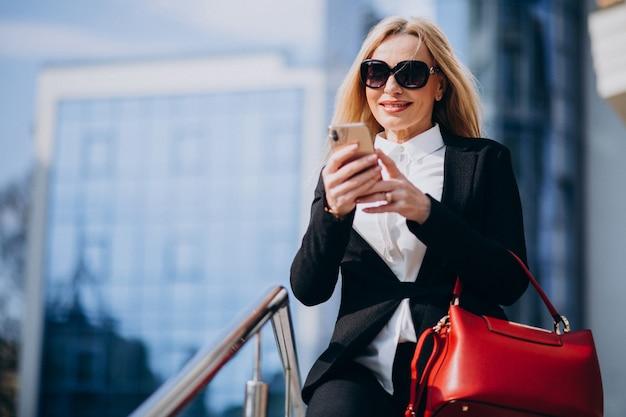 Mujer de negocios en traje elegante hablando por teléfono por el centro de negocios