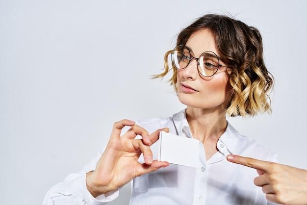 Mujer de negocios en traje y gafas posando, espacio ligero