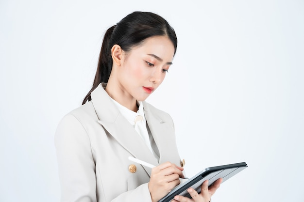 Mujer de negocios en traje gris con tableta y lápiz para registrar las actas de la reunión y el trabajo.