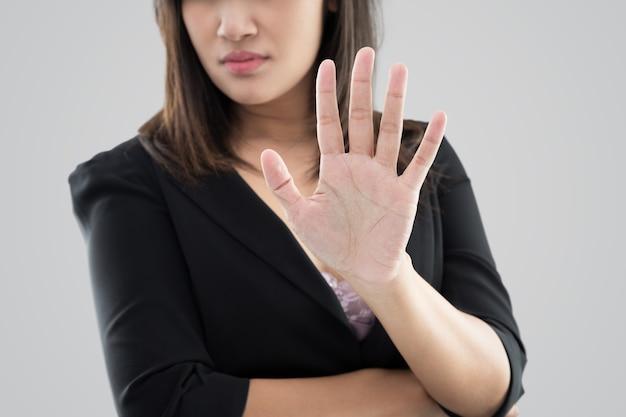 Mujer de negocios en traje negro que muestra su negación con no en su mano