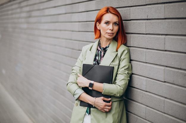 Mujer de negocios en traje verde de pie con carpeta