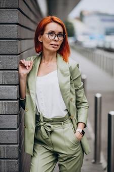 Mujer de negocios en traje verde de pie junto a la pared