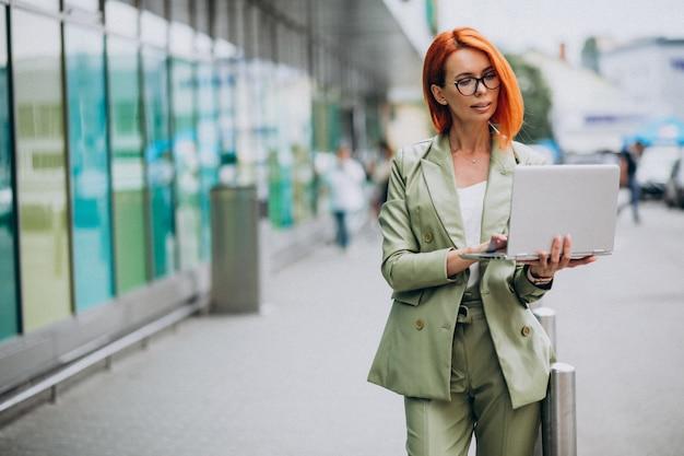 Mujer de negocios en traje verde de pie con laptop