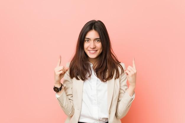 La mujer de negocios triguena joven contra un rosa indica con ambos dedos delanteros para arriba que muestran un espacio en blanco.