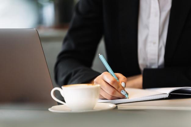 Mujer de negocios usando la computadora portátil escribiendo notas
