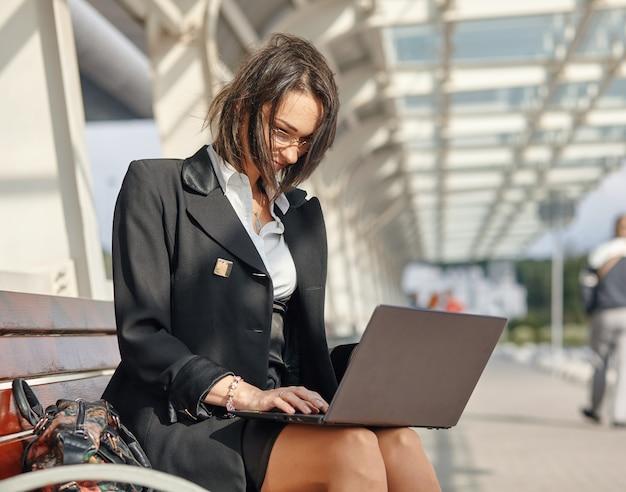 Una mujer de negocios usando una computadora portátil mientras está sentado en una calle de la ciudad moderna y arbolada
