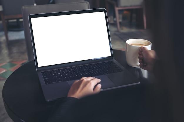 Mujer de negocios usando y escribiendo en la computadora portátil con pantalla blanca en blanco mientras toma café
