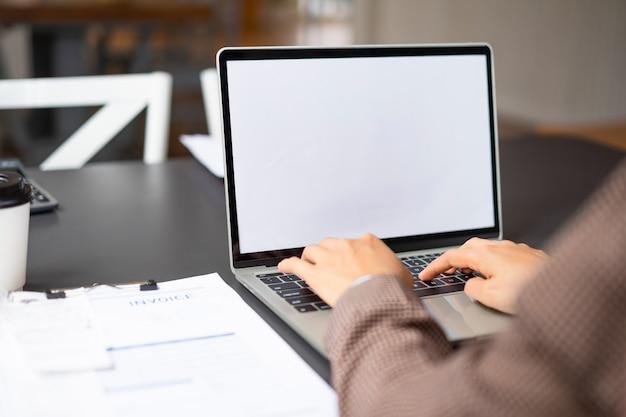 Mujer de negocios usando y escribiendo en la computadora portátil de pantalla blanca maqueta en su oficina.