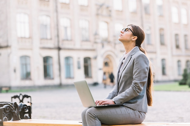 Mujer de negocios usando portátil al aire libre