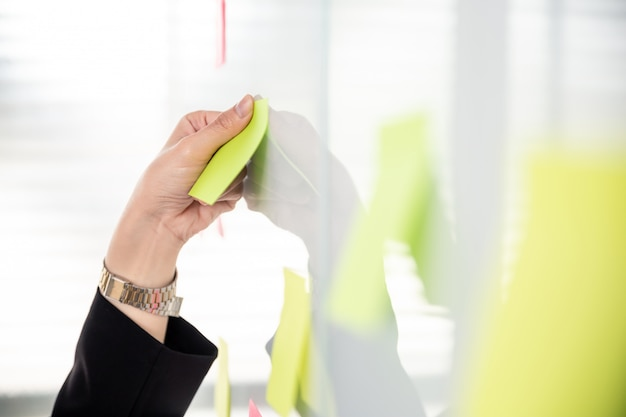 Mujer de negocios usando post-it nota sobre tablero blanco brillante.
