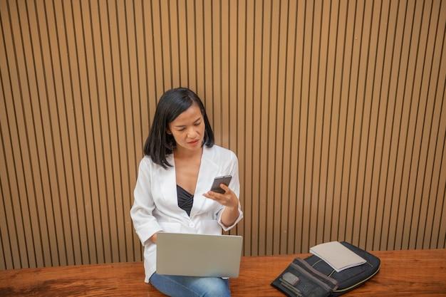 Mujer de negocios, utilizar, computadora portátil, y, hablar, con, teléfono celular