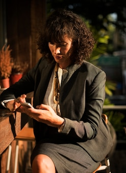 Mujer de negocios, utilizar, teléfono móvil, en, cafetería
