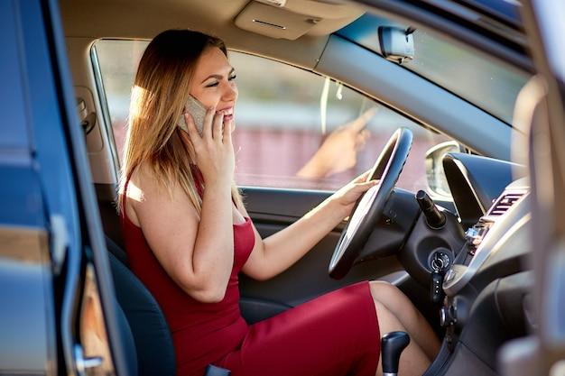 Mujer de negocios en un vestido rojo está sentado en el auto y hablando por teléfono