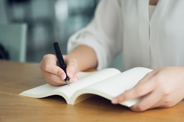 Mujer de negocios, viajero, escritor de artículos sostenga la pluma para escribir el texto