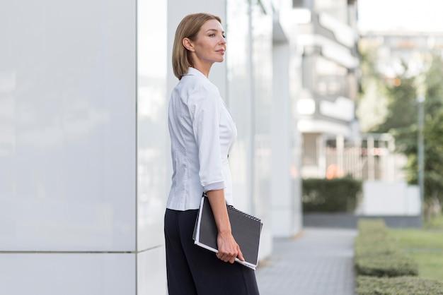 Mujer de negocios de vista lateral con archivo