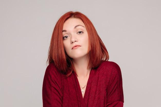 Mujer de negocios vistiendo en rojo con emoción pasiva y mirando frustrado.