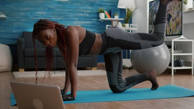 Mujer negra adulta sentada en el mapa de yoga viendo ejercicios de fitness en línea