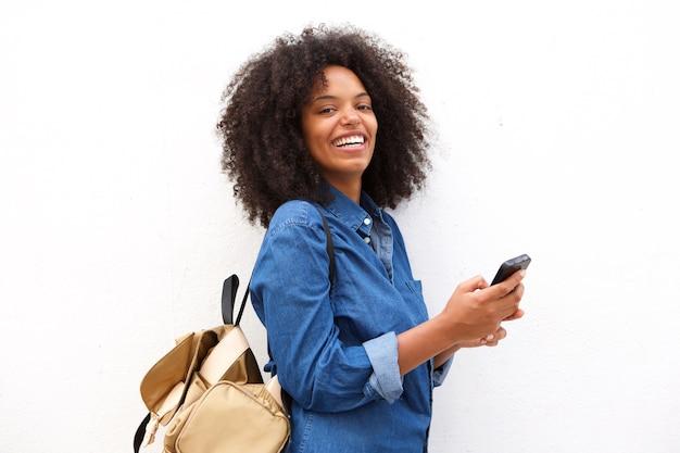 Mujer negra alegre con la mochila que sostiene el teléfono móvil