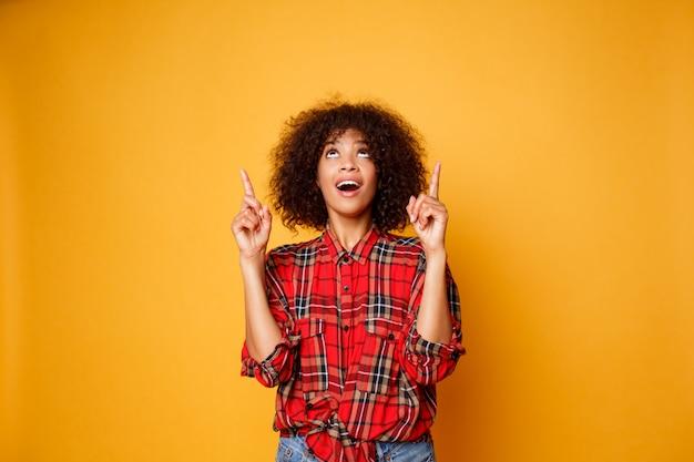 Mujer negra americana alegre en la camisa roja que mira hacia arriba y que señala los dedos para arriba en el espacio de la copia aislado sobre fondo anaranjado.