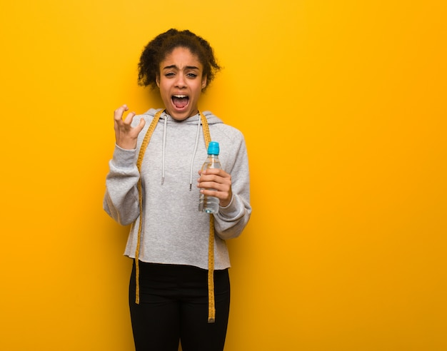 Mujer negra de la aptitud joven muy asustada y asustada. sostener una botella de agua.