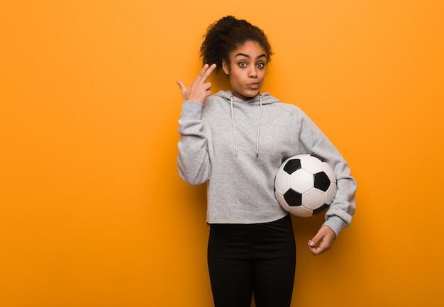 Mujer negra de la aptitud joven que hace un gesto del suicidio. sosteniendo un balón de fútbol.