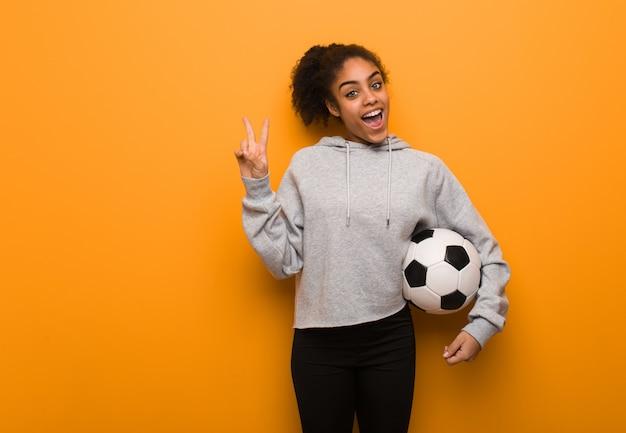 Mujer negra de la aptitud joven que hace un gesto de la victoria. sosteniendo un balón de fútbol.
