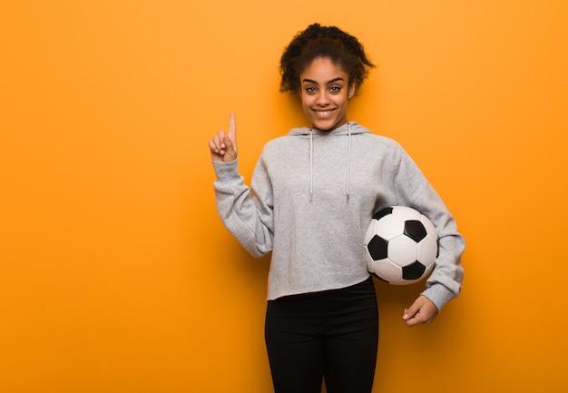 Mujer negra de la aptitud joven que muestra el número uno. sosteniendo un balón de fútbol.