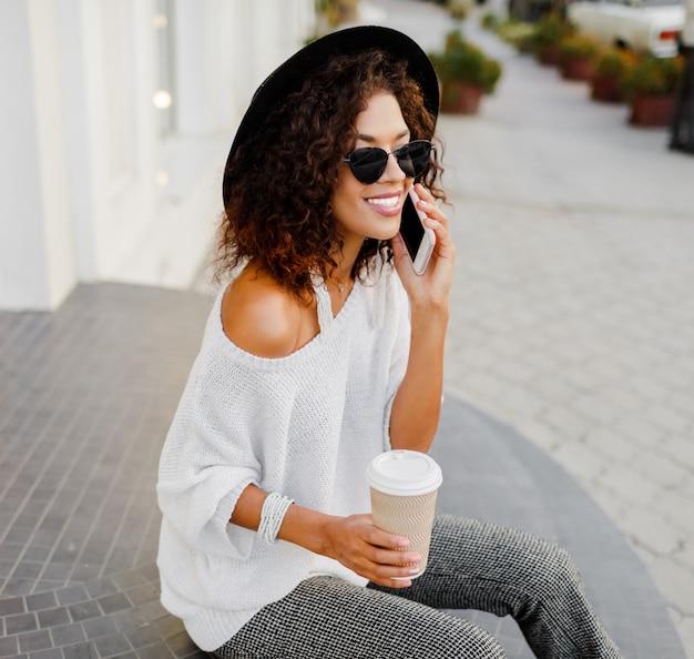 Mujer negra, blogger o gerente de la tienda hablando por teléfono móvil durante el descanso para tomar café. sentado en las escaleras y sosteniendo la taza de papel de bebida caliente. traje de moda blanco y negro.