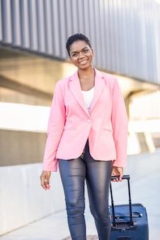 Mujer negra caminando con bolsa de viaje con chaqueta rosa.