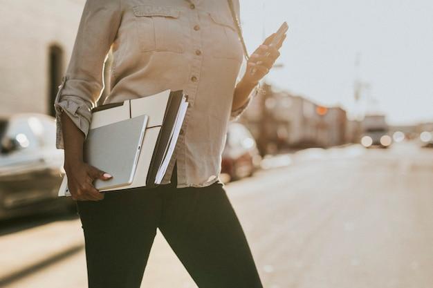 Mujer negra con carpetas de archivos cruzando una calle mientras usa su teléfono