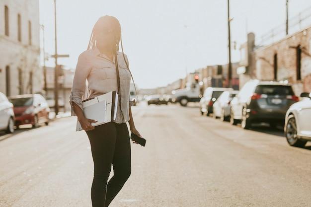 Mujer negra con carpetas de archivos cruzando una calle