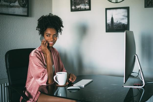 Mujer negra en casa trabajando con computadora y café en la mañana