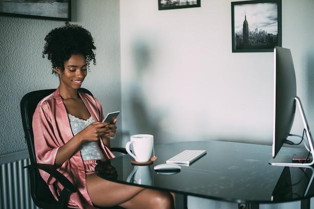 Mujer negra en casa trabajando con computadora, teléfono inteligente y café en la mañana