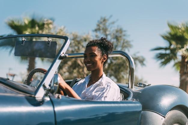 Mujer negra conduciendo un coche descapotable vintage