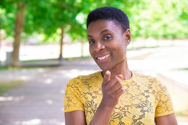 Mujer negra confiada sonriente que señala con el dedo a la cámara