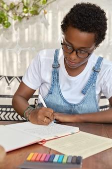 Mujer negra con corte de pelo juvenil, escribe en un cuaderno con bolígrafo, intenta completar el trabajo del curso
