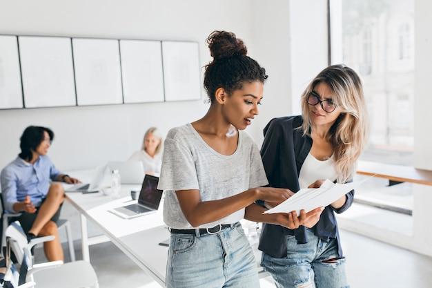 Mujer negra delgada en jeans explicando algo a la colega femenina europea mientras el hombre asiático habla con una joven rubia. retrato de gerentes de empresa internacional resolviendo problemas laborales.