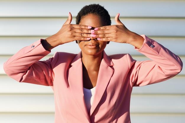 Mujer negra divertida que se coloca en la pared urbana que cubre sus ojos con sus manos.