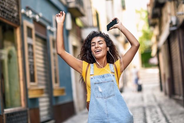 Mujer negra divertida que escucha la música con los auriculares al aire libre.