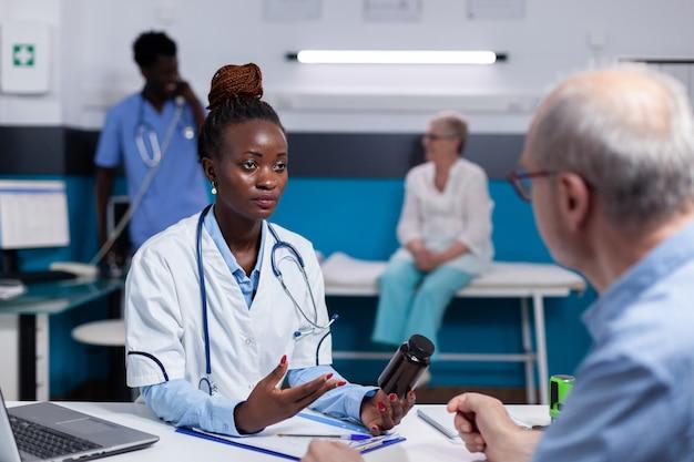 Mujer negra, con, doctor, profesión, tenencia, botella de píldoras