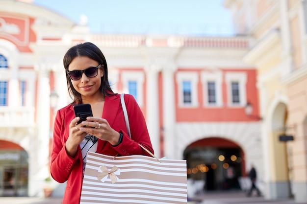 Mujer negra enviando mensajes de texto sms en el teléfono