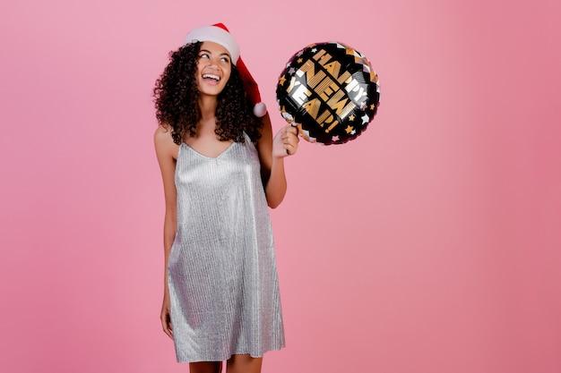 Mujer negra con feliz año nuevo globo con sombrero de navidad y vestido aislado en rosa