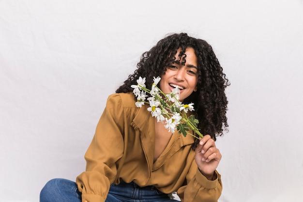 Mujer negra feliz que sostiene las flores de la margarita