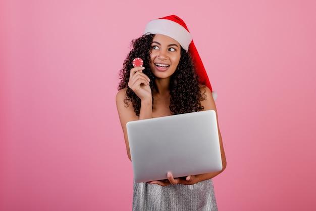 Mujer negra con fichas de póker de casino y portátil con sombrero de navidad de vacaciones y vestido aislado en rosa