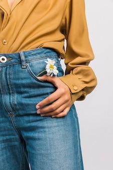 Mujer negra con flor de margarita en bolsillo de jeans