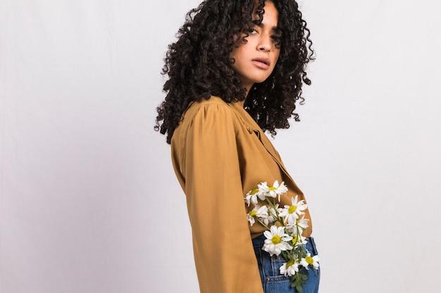 Mujer negra con flores en el bolsillo de los pantalones vaqueros.